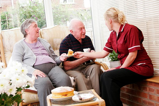 A care worker serves cake and tea to an elderly couple in a care home setting