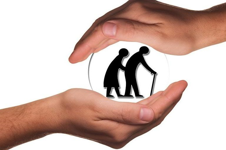 Hands cupping a silhouetted image of an old man and woman walking, symbolising care