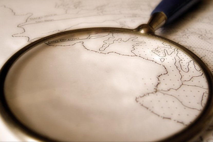Image of a magnifying glass magnifying a portion of a map