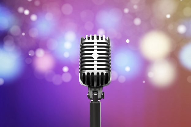 Microphone against multicoloured lights background