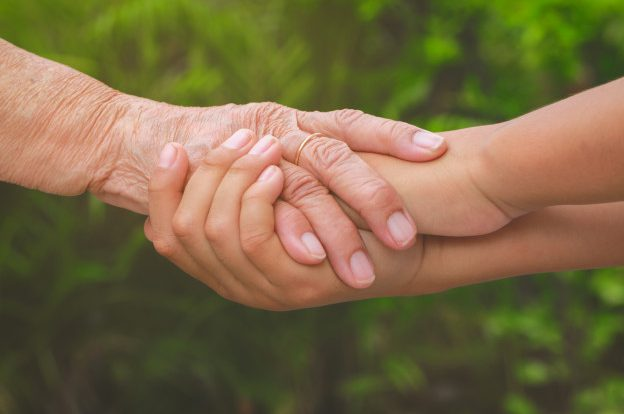 Old and young hands being held in a caring supportive way