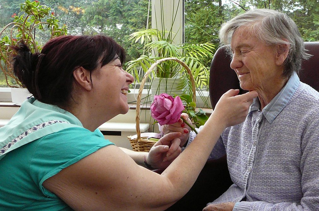 Care home carer smiling at resident