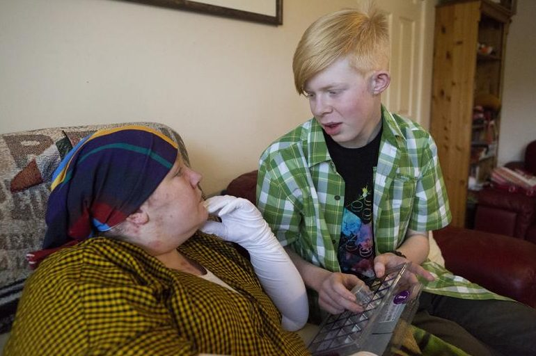 A young carer at home sitting and talking with his mother