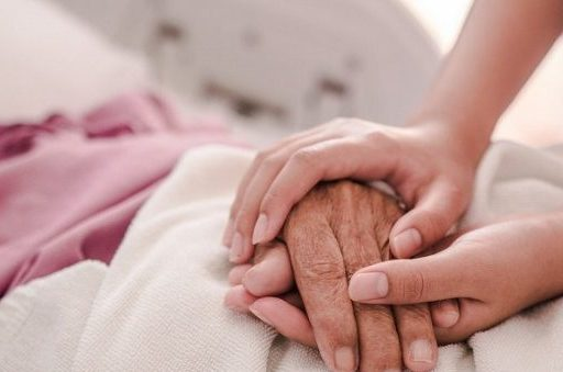 Care worker gently holding an elderly persons hand