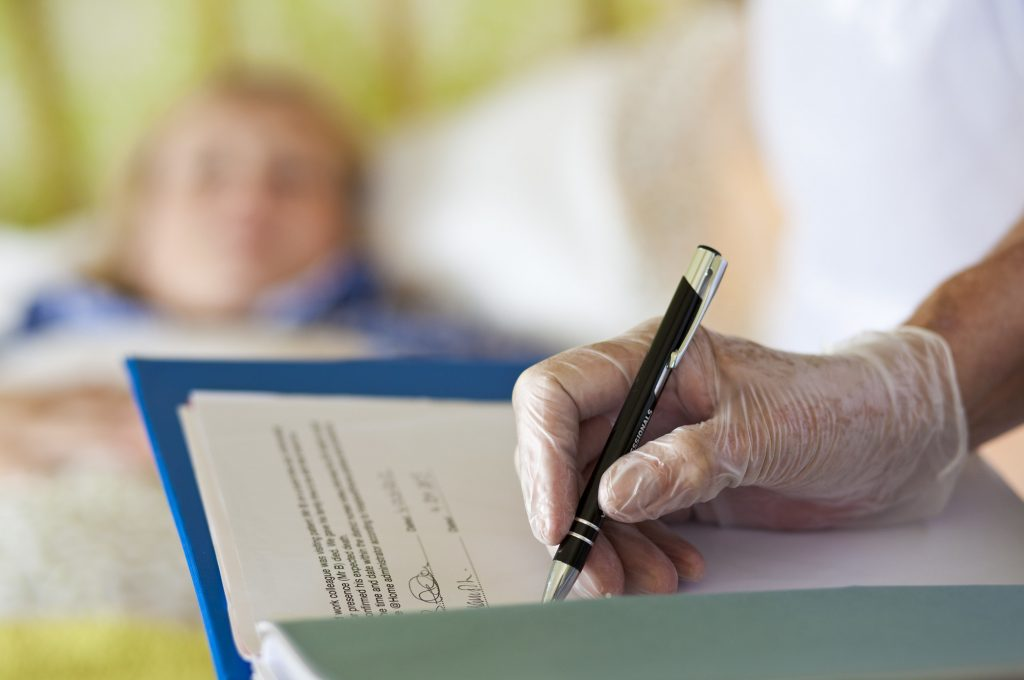 Care professional writing notes by bedside wearing surgical gloves