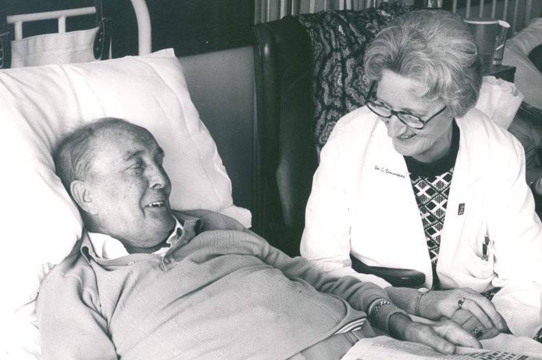 Dame Cicely Saunders at the bedside of a hospice resident.
