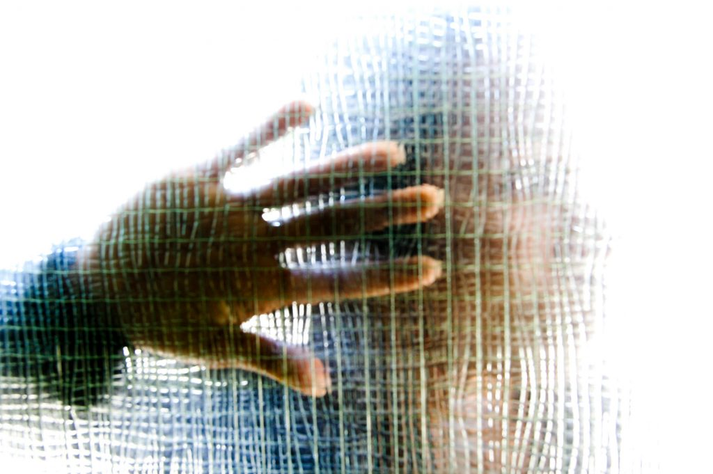 Woman with hand to glass panel in a front door