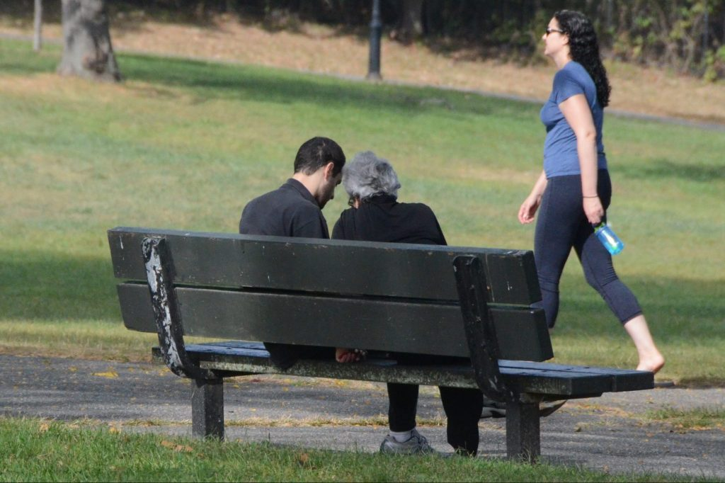A man and his mother sitting on a park bench