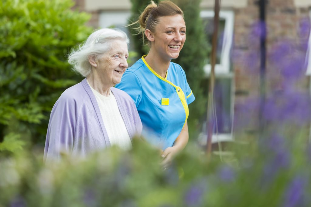Female resident and care team member walking in the gardens