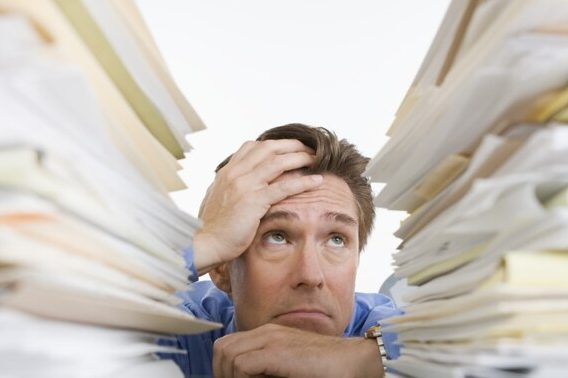 Man staring at mountains of paperwork