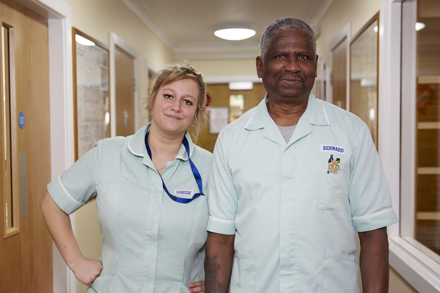 Two care workers in a care home corridor
