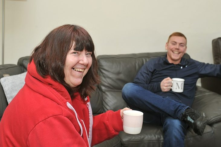 Two happy people enjoying a cup of tea
