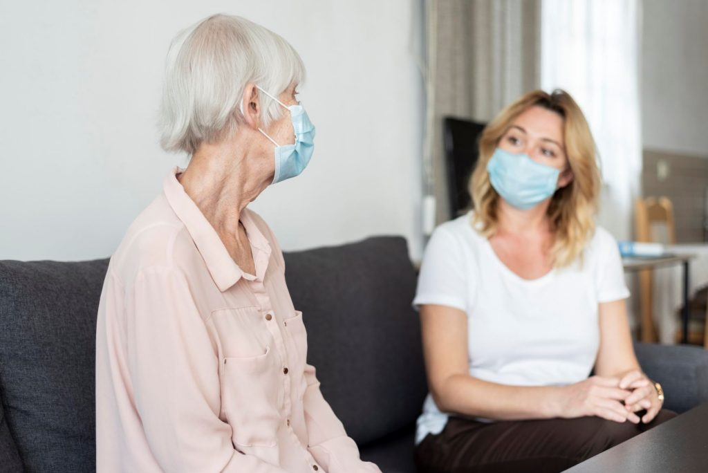 Woman visiting relative in care home, both wearing masks