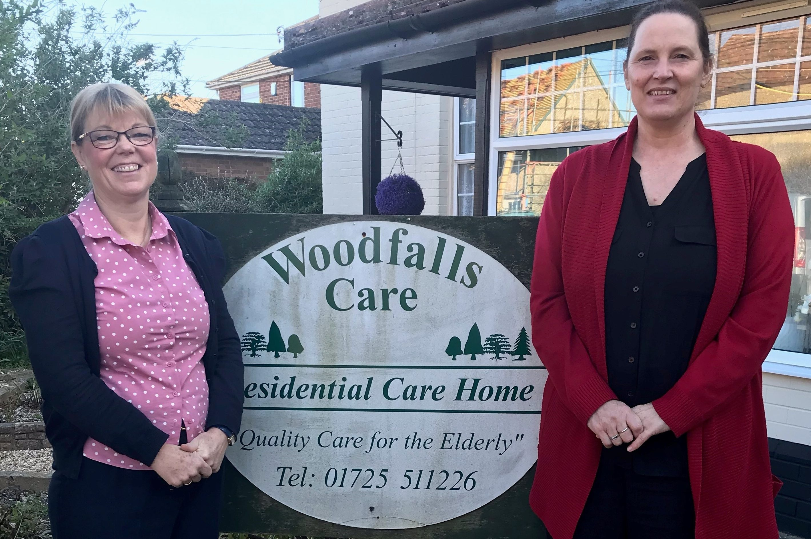 Alison and Pascalle standing beside the care home sign.