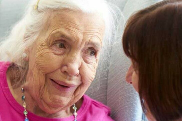 Care home resident talking to staff member