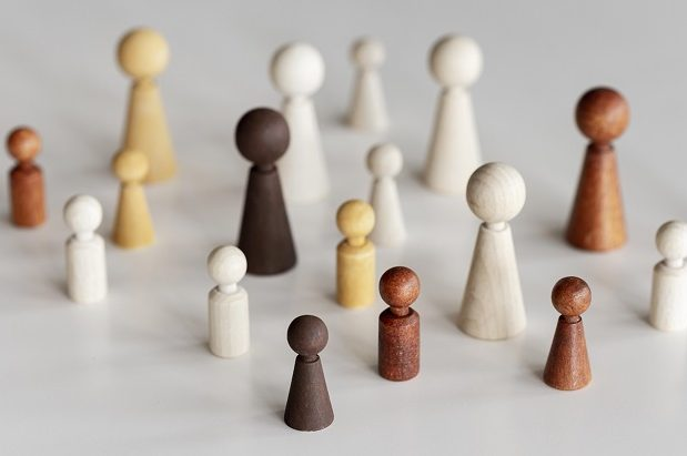wooden characters of different sizes and colours to highlight diversity