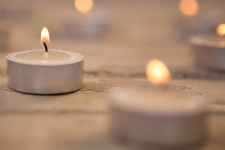 Candles burning on wooden plank