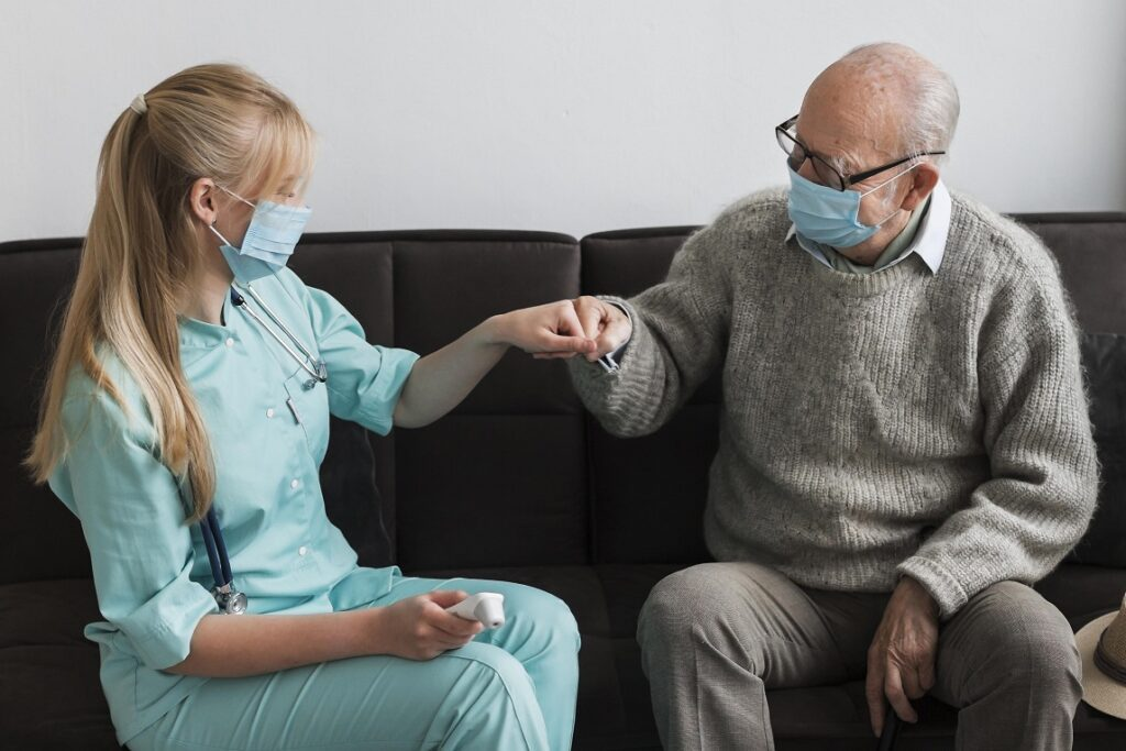 Care home worker and resident fist bump wearing masks